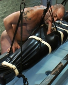 bound guy in latex getting blowjob