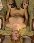 naked and upside down on a chair