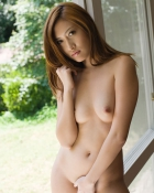 asian posing near a window